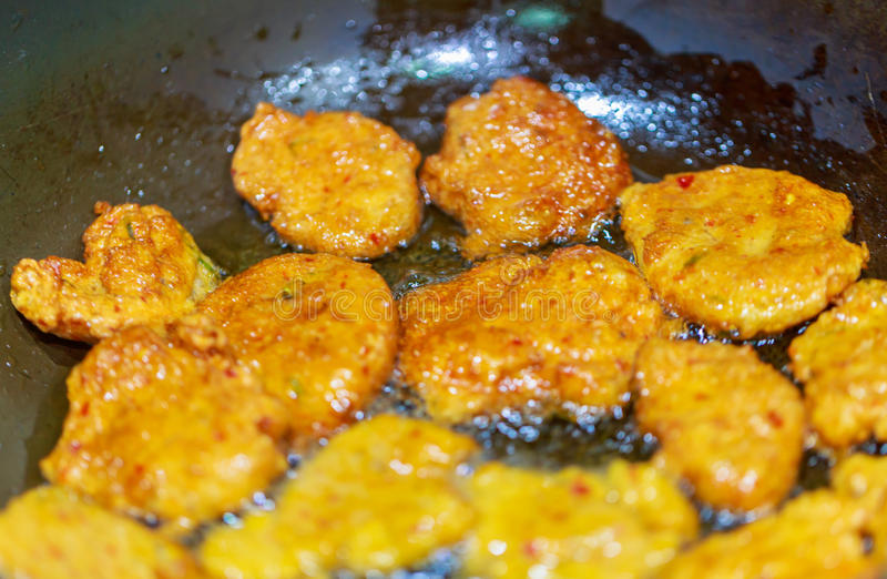 Deep fried fish cake in the pan, on stove, a famous Thai traditional food. stock photo