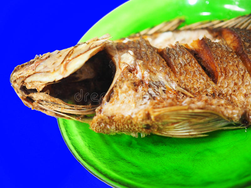 Deep fried fish head and belly on green dish, blue screen die cut stock photo
