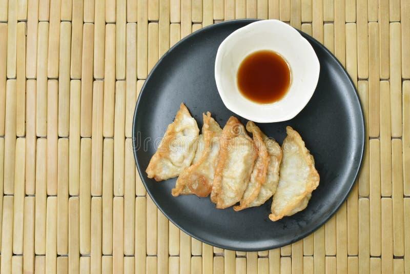 Deep fried Gyoza or Japanese dumpling stuffed minced pork dipping shoyu sauce on plate stock photos