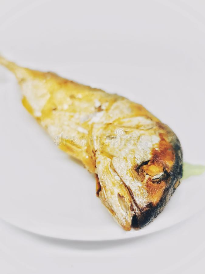 Deep fried mackerel Fish on the white Plate is regular Food Meal for Thai people in Bangkok. Deep fried mackerel Fish on the white Food Meal for Thai people in stock photos
