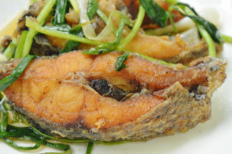 Deep fried Nile Tilapia or mango fish slice dressing soy sauce and spring onion on plate stock photos