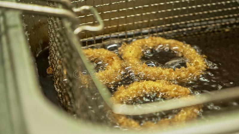 Deep fried onion ring. Oniony Rings cooking in hot bubbly oil in a deeped fryer. Golden chopped onions circle frying royalty free stock image