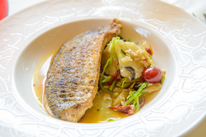 Deep fried sea-bass in plate stock images