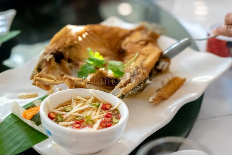 Deep fried seabass fish in black soy sauce,crispy fried fish stock photo