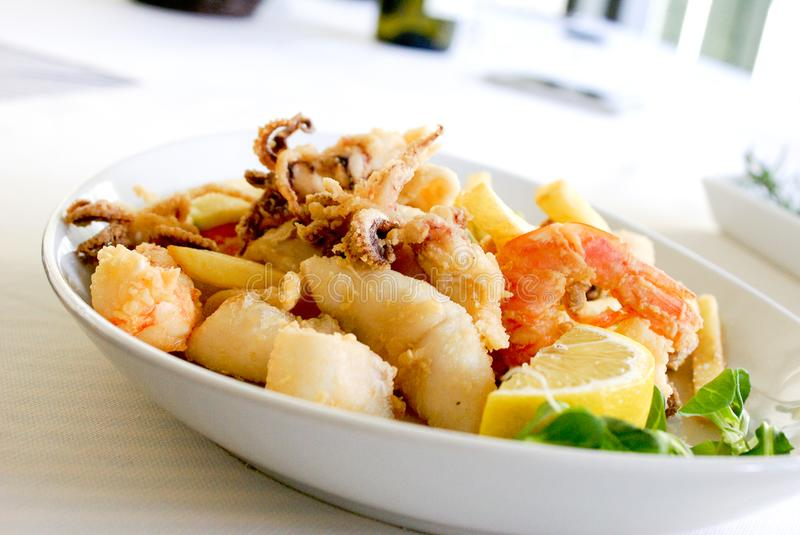 Deep Fried Shrimp and Squid With Slice of Lemon on Ceramic Plate royalty free stock image
