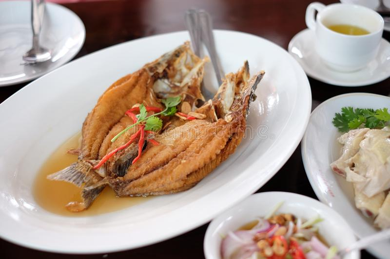 Deep fried snapper topped with fish sauce. stock photos