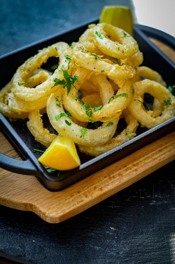 Squid rings deep fried with lemon wedges stock images