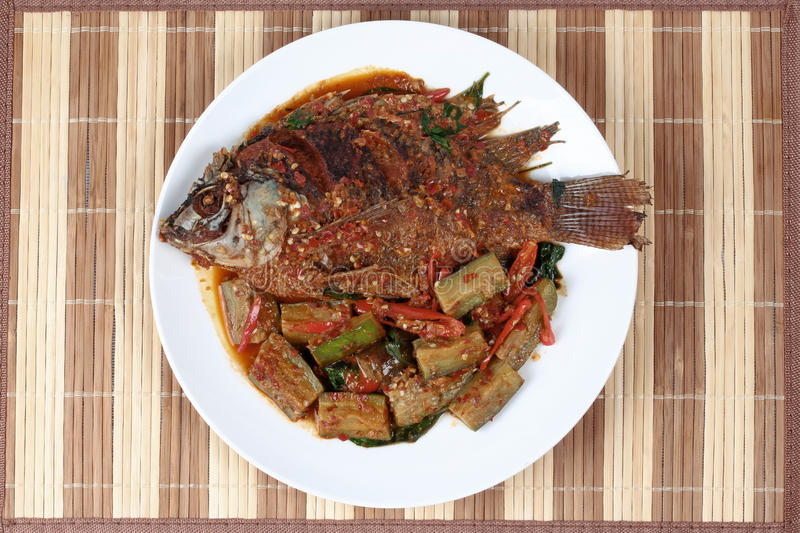 Deep-fried tilapia fish topped Spicy fried eggplant. royalty free stock photos