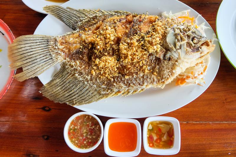 Deep fried tilapia topped with garlic and pepper, vegetable. royalty free stock photo