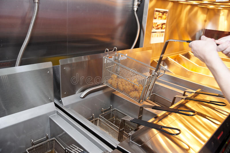 Deep fryer. With boiling oil on restaurant kitchen royalty free stock photo
