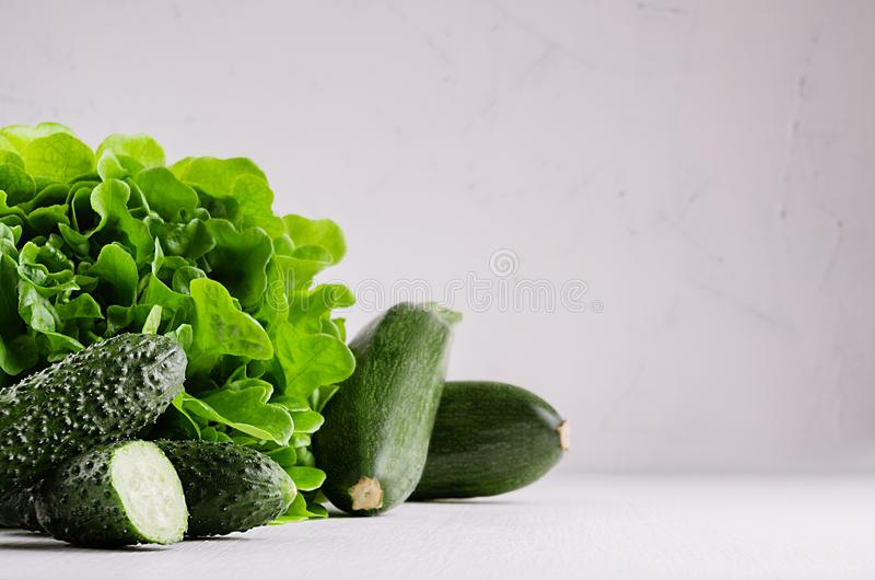 Deep green different vegetables on soft white wood table with copy space. royalty free stock image