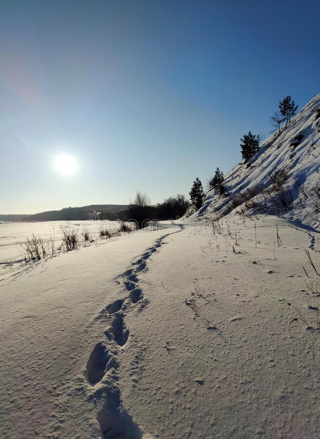Deep human footprints on the beautiful textured snow near the frozen river and slope. Against the background of the winter blue clear sky with the bright light stock photography