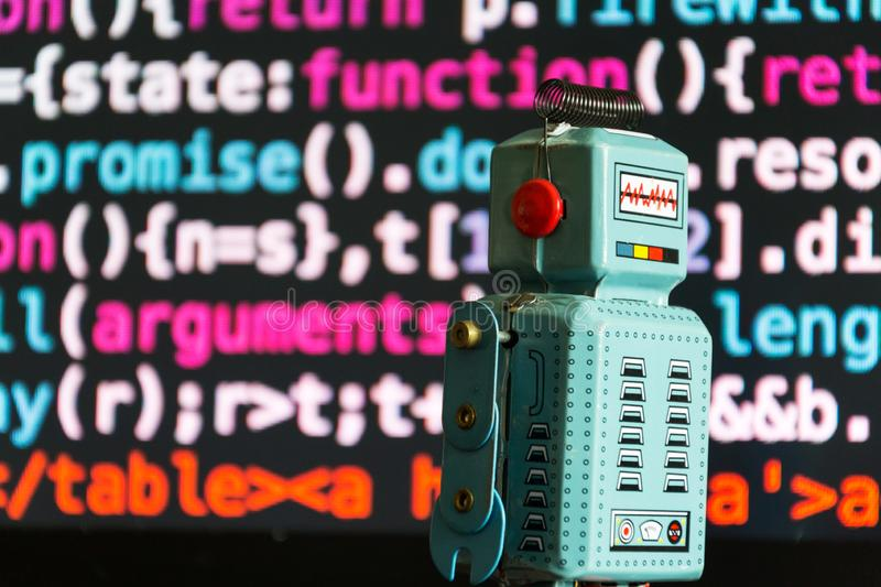Robot with source code screen, artificial intelligence, deep learning concept. Deep learning concept - robot looking at laptop screen with source code royalty free stock photo