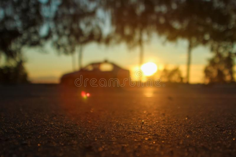 Deep morning dawn with highlights in the orange rays of the summer sun on the road against the trees grove on blurred background. In the light and cars stock photo