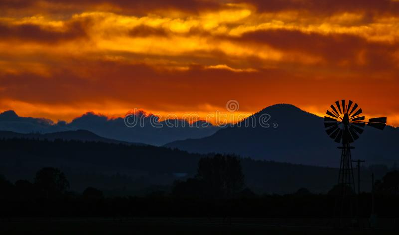 Deep orange sky with a contrasted country view of a windmill stock photo