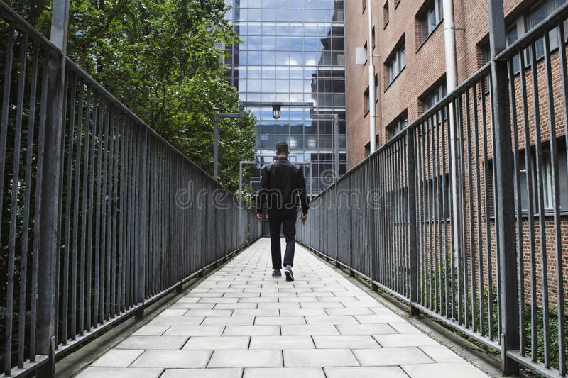 Deep perspective of a man walking between fences towards a hospital. royalty free stock image