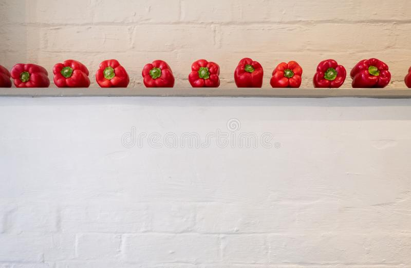 Deep red bell peppes lined up on a shelf in front of a white painted wall. Deep red bell peppes lined up on a shelf in front of a white painted wall, in rustic stock photography