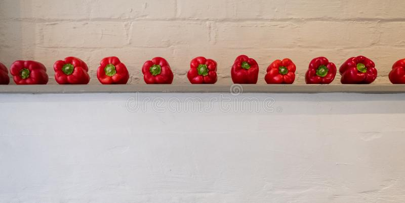 Deep red bell peppes lined up on a shelf in front of a white painted wall. Deep red bell peppes lined up on a shelf in front of a white painted wall, in rustic stock photos