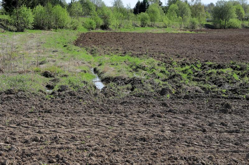 Deep ruts filled with water at the edge of a plowed field.  royalty free stock photos