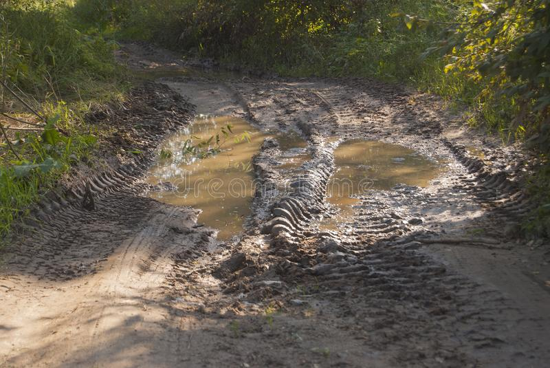 Deep ruts on the road filled with water. Difficultly passable dirty place royalty free stock image