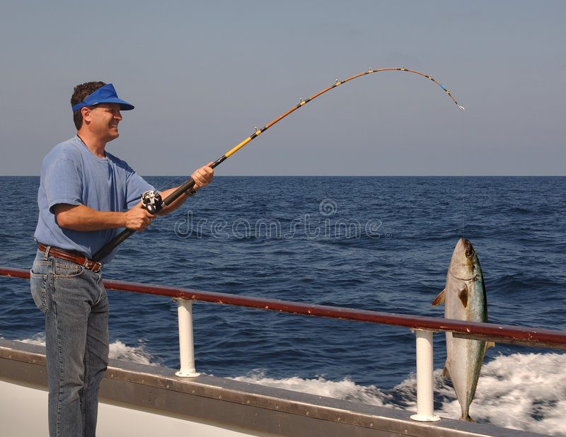 Deep Sea Fishing. Man fishing from the edge of a moving boat with a live yellow tail tuna hanging from the fishing line