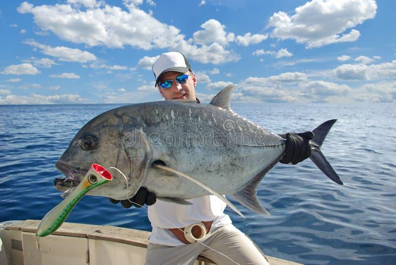 Deep sea fishing, popping, trevally jack. Deep sea fishing, big game fishing. Happy fisherman holding a trevally fish royalty free stock photo