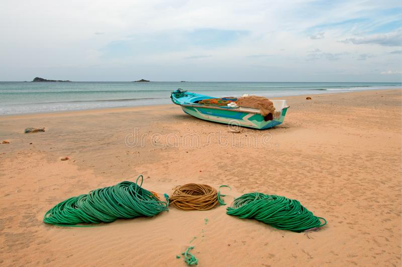 Deep sea fishing boat next to ropes and nets on Nilaveli Beach in Trincomalee state in Sri Lanka. Asia stock photo