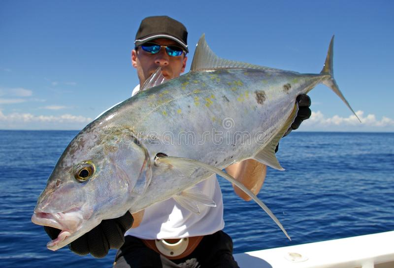 Deep sea fishing. Trevally jack. Catch of fish. Big game fishing, boat fishing, lure fishing. Fisherman holding a big Trevally jack royalty free stock images
