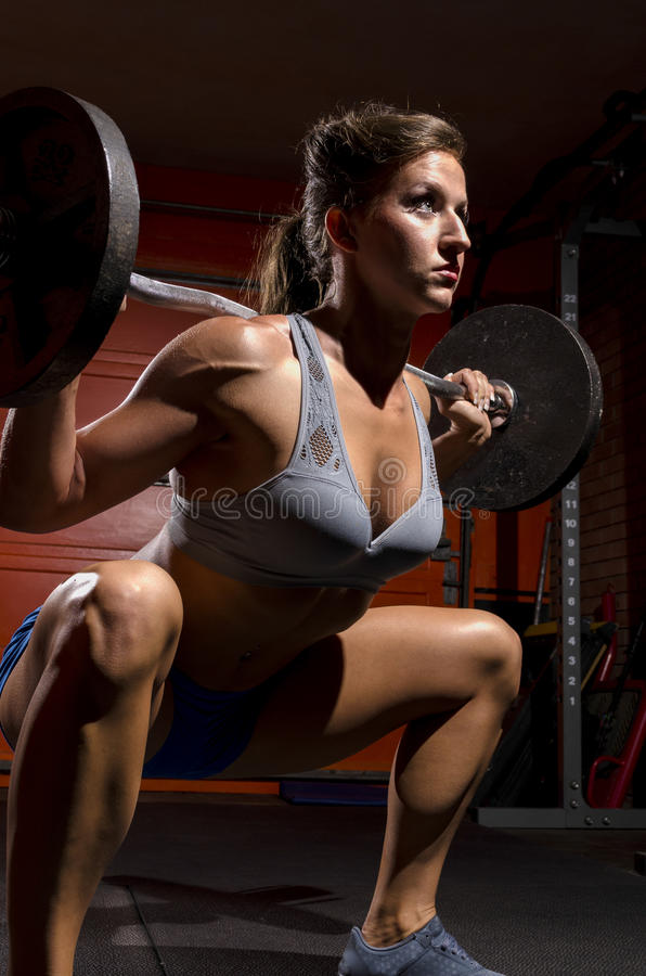 Deep Squat close. A fit woman doing a deep squat working out royalty free stock image