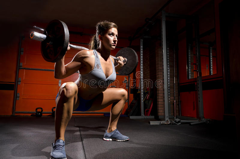 Deep Squat. A fit woman doing a deep squat working out stock photo