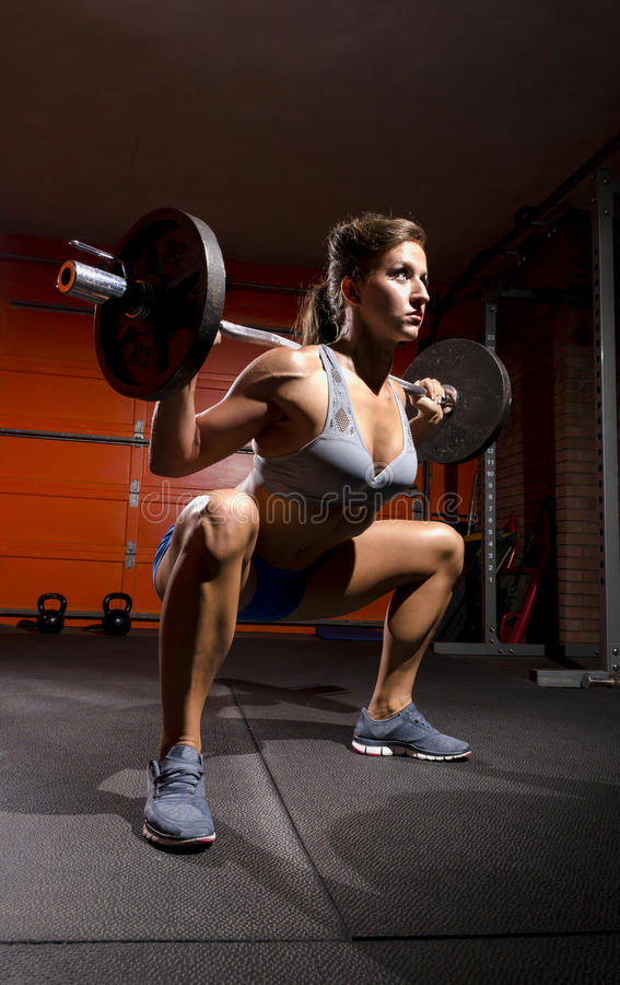 Deep Squat low view. A fit woman doing a deep squat working out royalty free stock photos
