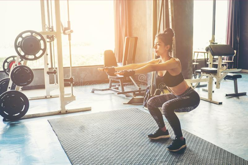 Deep squat of young beautiful woman in sportswear doing squat while standing in front of glass at gym.  stock photos