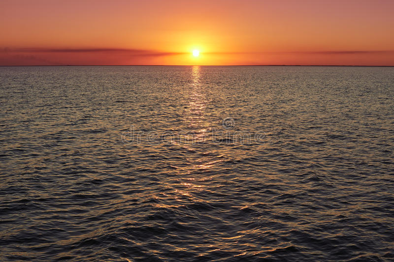 Deep sunset over calm smooth sea with bright colors and plenty of copy space. Beautiful natural summer seascape. Image of sunset w royalty free stock image