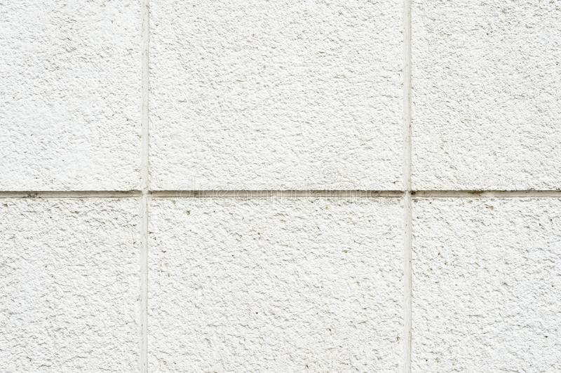 Deep texture of a white painted porous stone on the facade of the building. Finishing the facade of the building into. Square sections. Texture background with royalty free stock photo