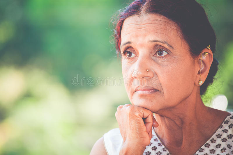 Deep thinker. Closeup portrait, morose elderly lady, daydreaming about the future looking ahead, resting face on hand, isolated green trees outdoors background royalty free stock photo