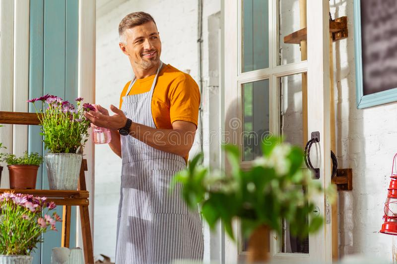 Handsome florist sprinkling flowers looking away with a smile. Deep in thought. Handsome florist sprinkling flowers on a shelve stand outside and looking away royalty free stock image