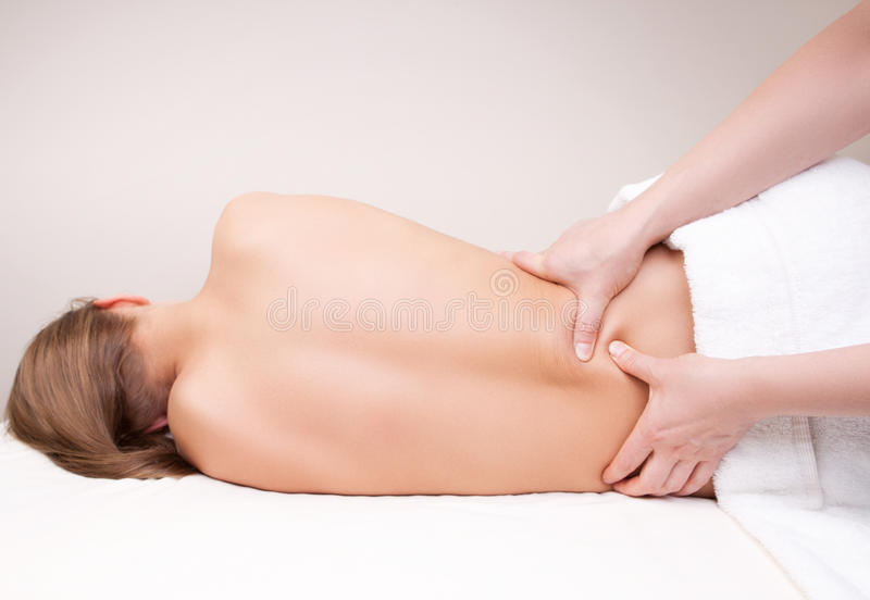 Deep tissue massage on the woman's lower back. On quadratus lumborum muscle royalty free stock photo