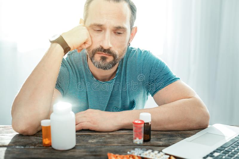 Deep upset man holding hand near head looking on pills. Hard to be healthy. Deep upset handsome man sitting by the table holding hand near head looking on pills stock photos