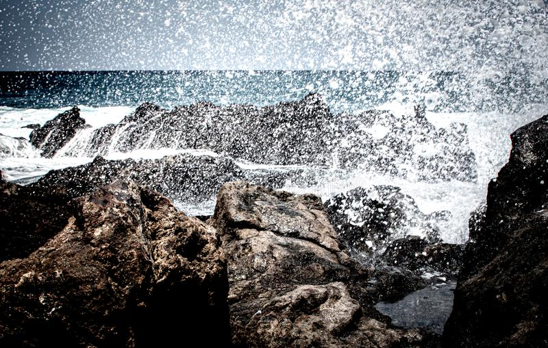 Deep view over lava rocks with breaking of waves royalty free stock image