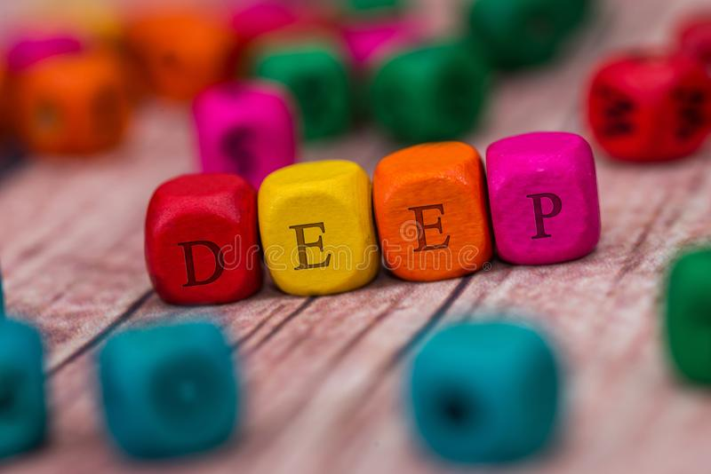Deep - word created with colored wooden cubes on desk.  royalty free stock images