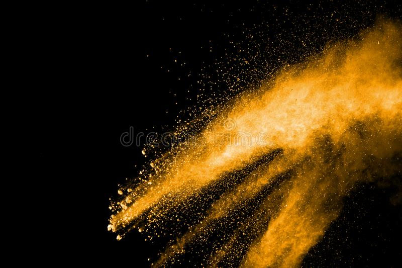Deep yellow dust particle splattered on black background. Orange color powder explosion on black background. Deep yellow dust particle splattered on black royalty free stock images