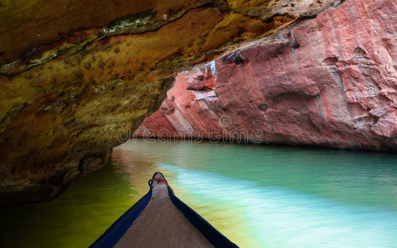Deeper in the narrow canyon. Canoe going deeper into a narrow canyon, almost getting stuck on it