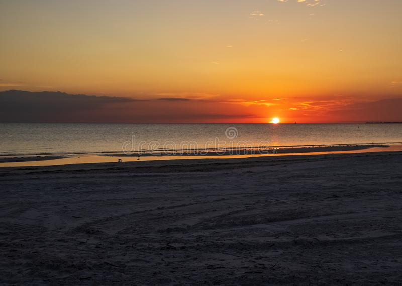 Deeply color sunset over the Gulf of Mexico on Fort Myers Beach. In FL with sailboat silhouette in distance stock images