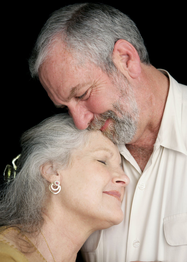 Deeply In Love. A beautiful middle aged couple tenderly embracing eachother. They are very much in love. Black background