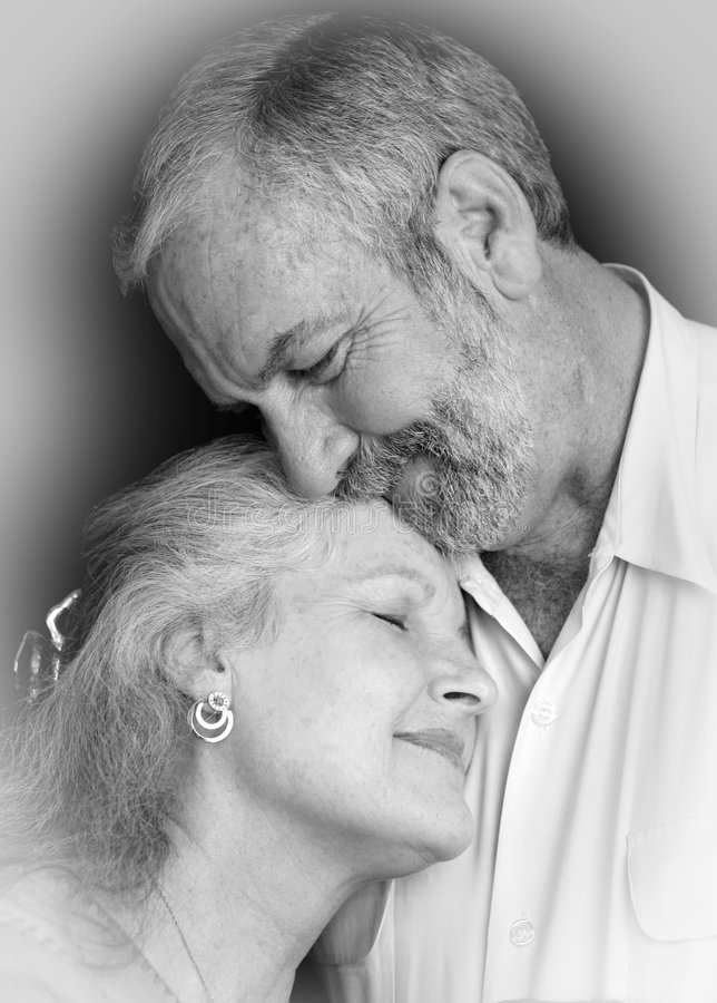 Deeply In Love. A beautiful middle aged couple tenderly embracing eachother. They are very much in love. Black background royalty free stock image