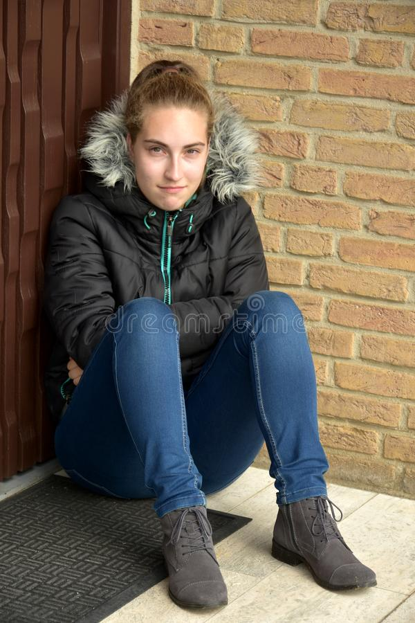 Deeply offended teenager pouts to herself. Unhappy teenage girl squats in a corner and feels all alone stock photography