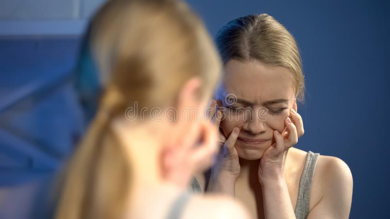 Deeply upset young woman looking sadly mirror, unhappy with appearance, puberty stock photo
