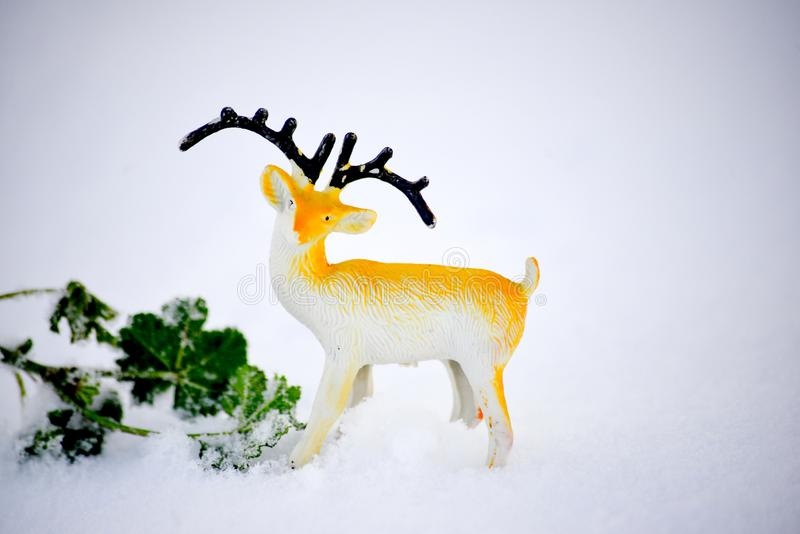 Deer figurine toy on a snow, winter theme. Image stock image