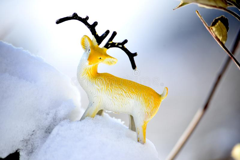 Deer figurine toy on a snow, winter theme. Image royalty free stock images