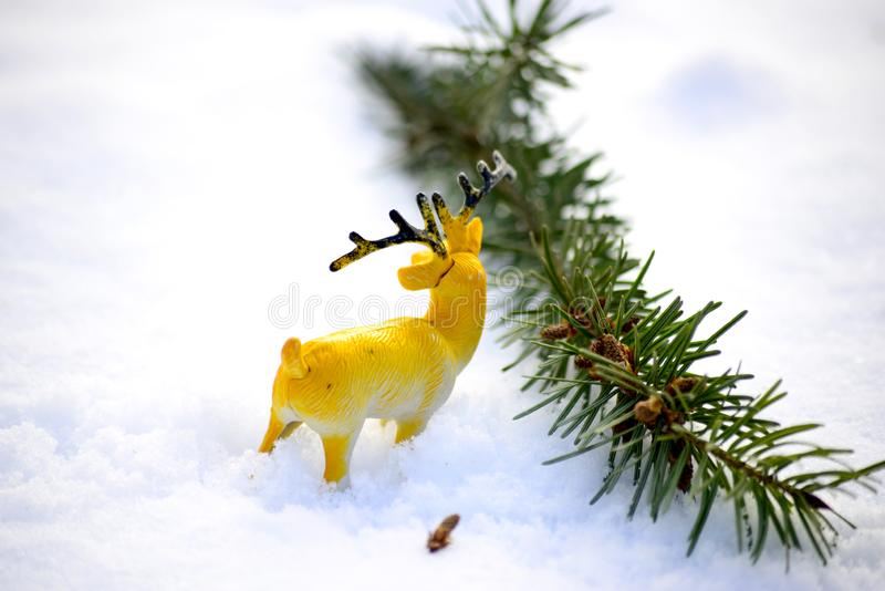 Deer figurine toy on a snow, winter theme. Image stock photo